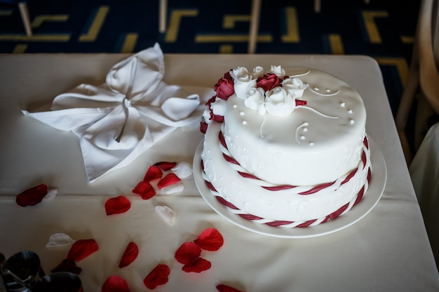 Wedding cake on the table with red pertals of red rose. marriage ceremony
