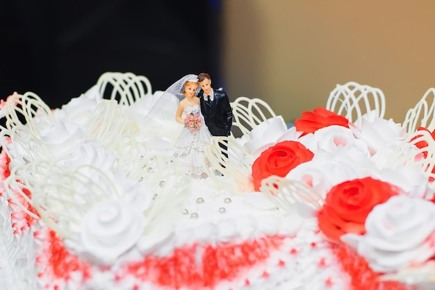 Wedding cake white cream decorated with red roses with figures of the bride and groom