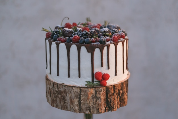 A wedding cake with berries, poured with chocolate on a shelf made of wood.