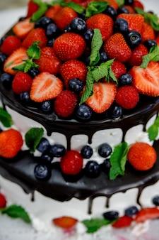 Свадебный торт с черникой и клубникой, залитый шоколадом и листьями мяты