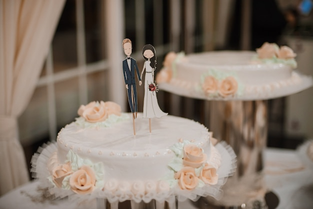 Wedding cake with funny figurines of groom and bride.