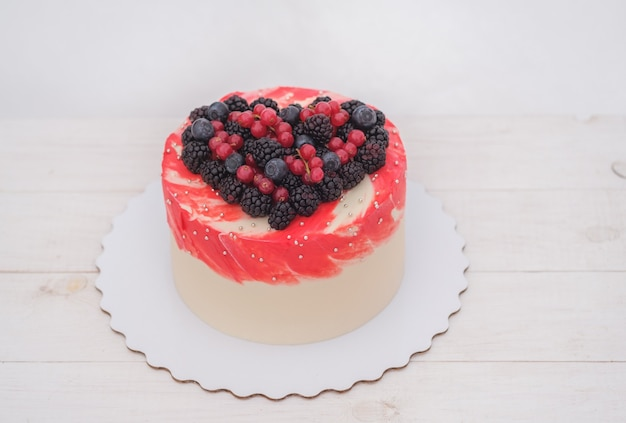 Wedding cake with natural berries laid out in the shape of a heart