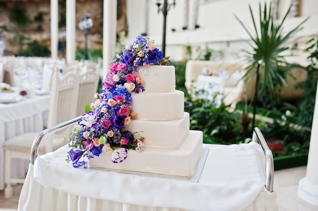 Wedding cake with purple and violet flowers at hall