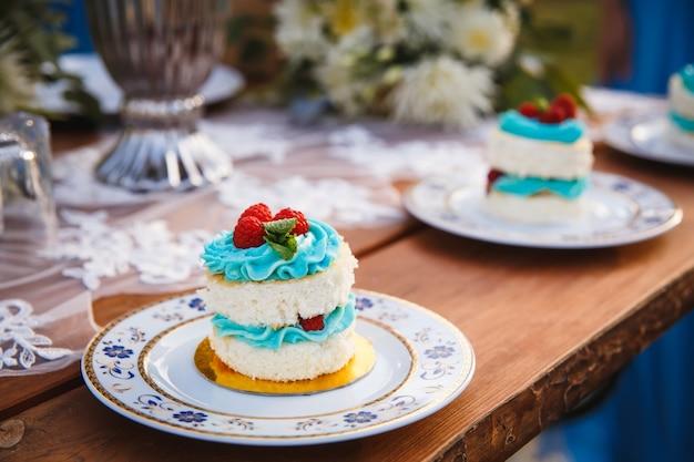 木製のお祝いのテーブルにラズベリーとウエディングケーキ Premium写真