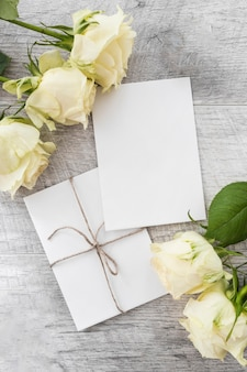 Wedding cards with roses on wooden background