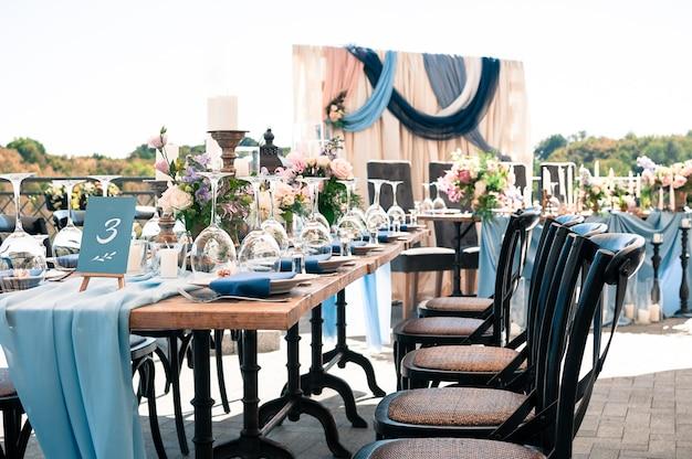결혼식 케이터링 이벤트 장식 꽃 양초 파란색 냅킨 나무 테이블 화창한 여름 날