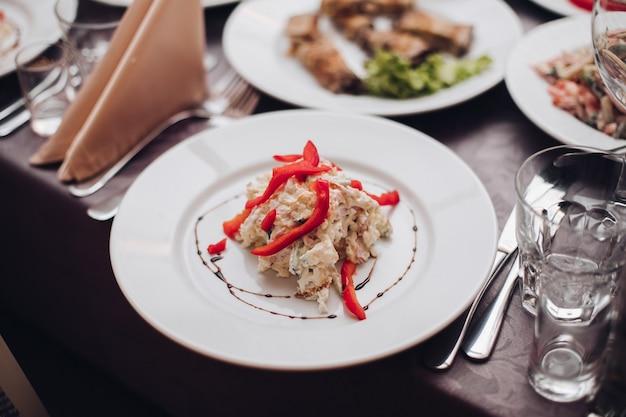 結婚式のケータリング。クローズアップで上に赤唐辛子とおいしいサラダと白いセラミックプレート。
