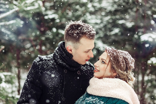 Wedding caucasian couple in winter season close up portrait outdoors. loving cute tender couple in love walking in showy forest together