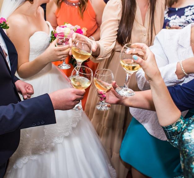 Празднование свадьбы. руки держат бокалы с шампанским и тостами