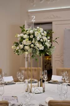 Свадебные украшения с металлической вазой и белыми свежими цветами.