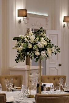 金属製の花瓶と白い生花のアレンジメントを備えた結婚式のセンターピース。
