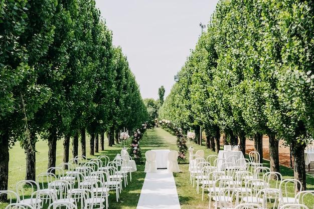 의자와 푸른 잔디에 꽃 아치가있는 결혼식 통로