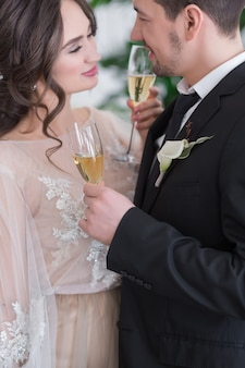 Wedding ceremony, bride and groom with champagne glasses.