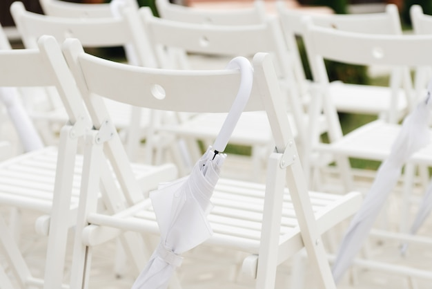 Wedding ceremony decor concept, wedding reception chairs and white umbrellas in case of rain