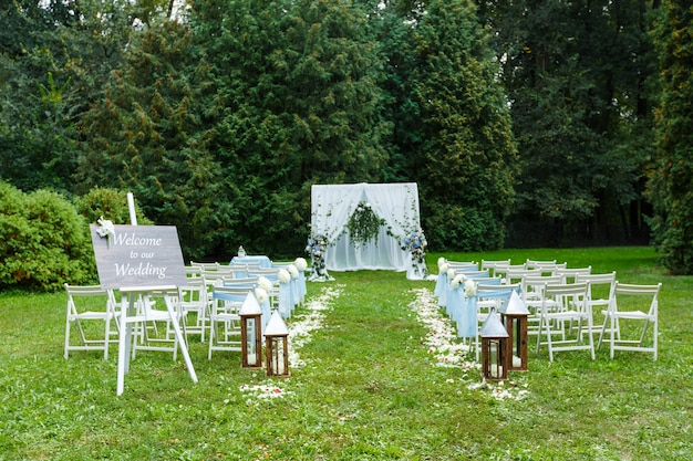 Wedding ceremony decorations arch chairs pointer and a lot of flowers in white and blue style