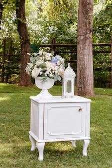 Wedding ceremony decorations bouquet of roses, glasses in park outdoors.
