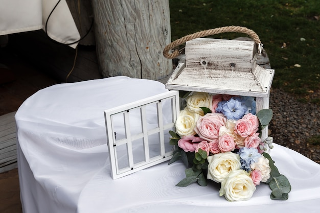 Wedding ceremony decorations bouquet of roses at the table outdoors.
