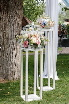 Wedding ceremony decorations bouquets of roses and eustoma in restaurant outdoors.