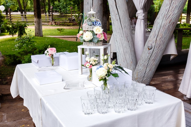 Wedding ceremony decorations bouquets of roses, glasses in restaurant outdoors.