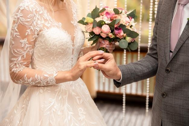 結婚式。新郎は花嫁の指に結婚指輪を置く