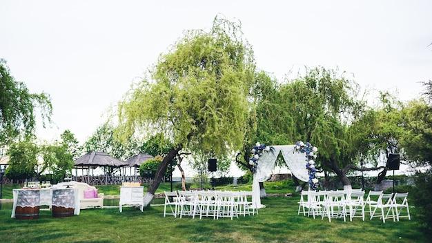 自然の中での結婚式:アーチ、ゲスト用の椅子、ビュッフェテーブル、フォトゾーン。