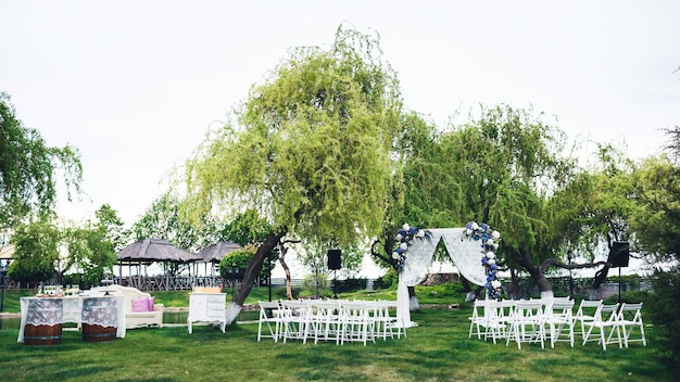 Wedding ceremony in nature: an arch, chairs for guests, a buffet table, a photozone.
