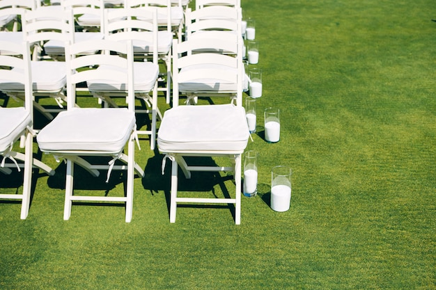 Wedding ceremony in nature. rows of white chairs on the lawn.