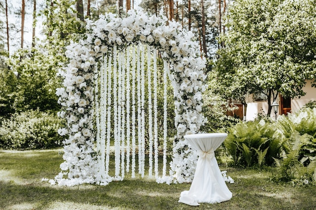 Wedding ceremony in nature with an arch decorated with white flowers