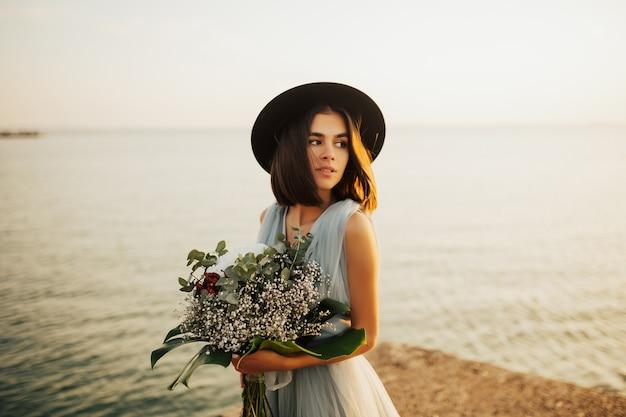 海のビーチでの結婚式。花嫁はウェディングブーケを持っています。