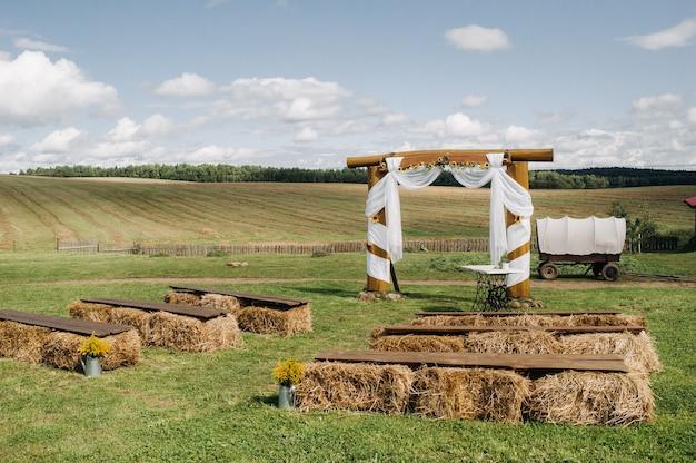 마을 들판의 거리에서 결혼식 건초 더미와 결혼식 카트로 장식하십시오.