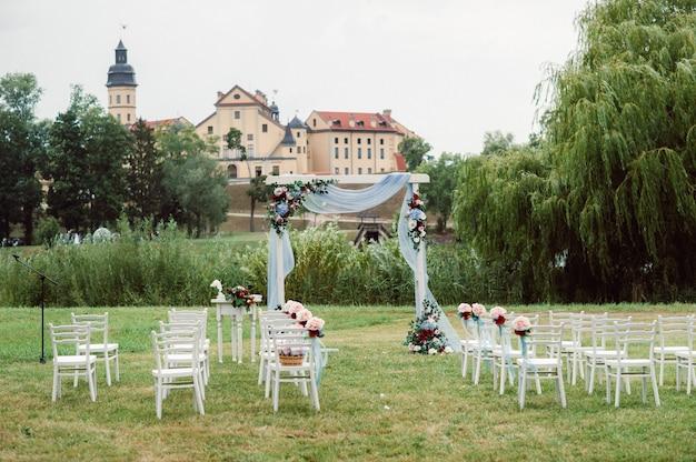 Свадебная церемония на улице на зеленой лужайке. декор живыми цветами арки для церемонии.