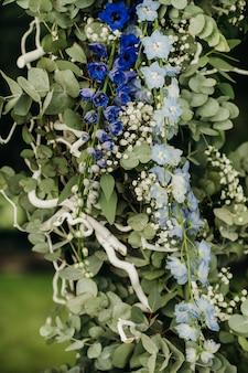 緑の芝生の路上での結婚式。式典のための新鮮な花のアーチで飾る。