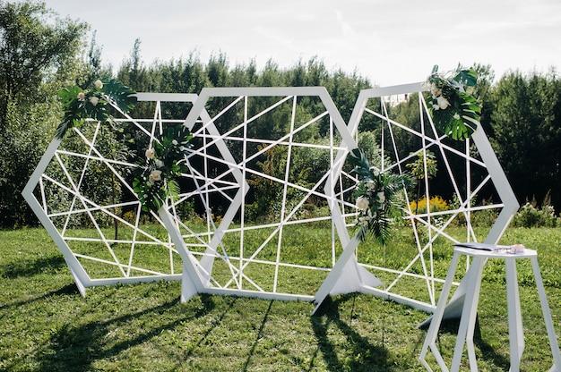 녹색 잔디밭에서 거리에서 결혼식을 올릴 수 있으며, 결혼식을 위해 신선한 꽃 아치로 장식하십시오.