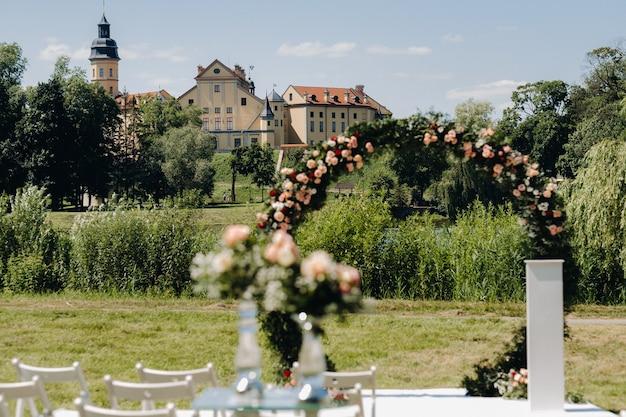 ネスヴィシ城近くの緑の芝生の路上での結婚式。ベラルーシ。