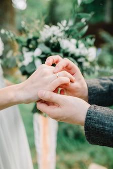 結婚式や婚約の概念。結婚指輪交換。新郎と新婦はブライダルリングをつけました。