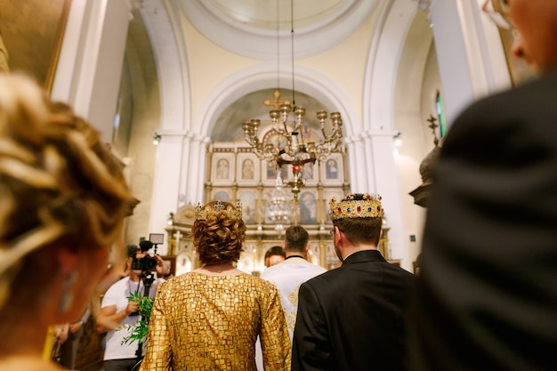 Wedding ceremony in an orthodox church the groom the bride and the priest in a cassock stand in the