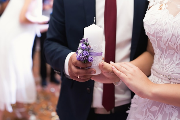 Wedding ceremony, paraphernalia, the bride and groom hold a large candle in their hand