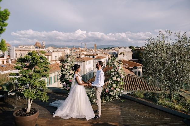 A wedding ceremony on the roof of the building, with cityscape views of the city and the cathedral of santa maria del fiore