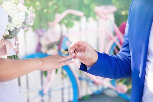Свадебная церемония жених надевает кольцо на палец невесты праздник