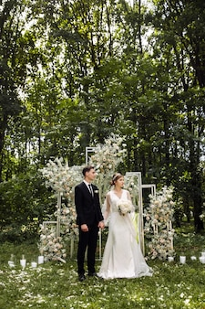신혼 부부가 서있는 결혼식. 신랑과 신부가 결혼식 중에 길거리에 있습니다. 꽃으로 장식 된 웨딩 아치에 의해 신혼 부부. 야외 결혼식