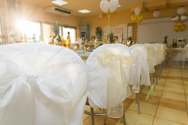 金色のリボンで飾られた列の結婚式の椅子