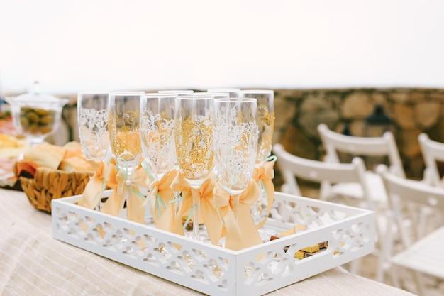 탁자 위의 투각 흰색 쟁반에 패턴과 베이지색 활이 있는 웨딩 샴페인 잔