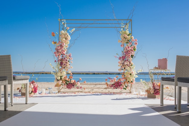 Wedding chuppa at riverside decorated with fresh flowers.