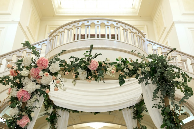 Wedding chuppah decorated with fresh flowers indoor banquet hall of wedding ceremony.