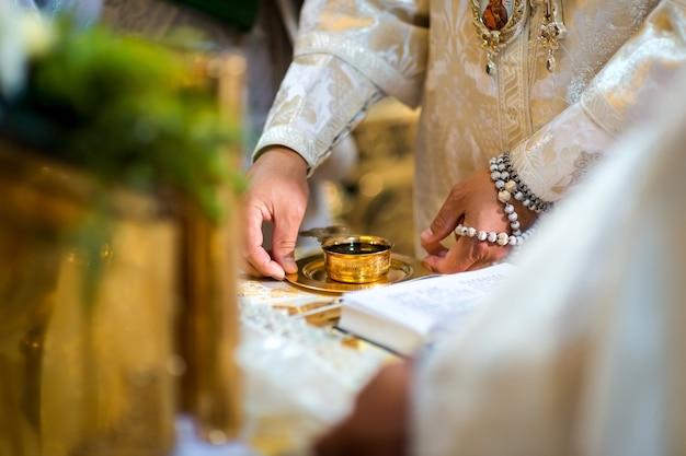 結婚式の教会の式典のコンセプト。皿につるのある黄金のカップ。背景がぼやけている。閉じる。