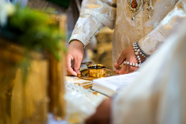 Wedding church ceremony concept. golden cup with vine on the plate. blurred background. closeup.