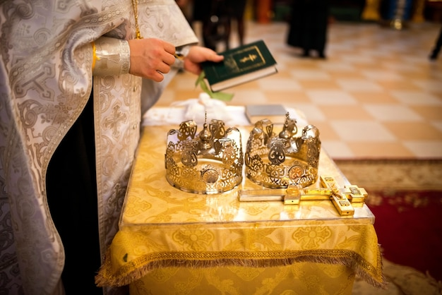 結婚式の教会の式典のコンセプト。プレート上の金の指輪。背景がぼやけている。閉じる。