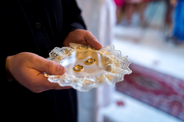 Wedding church ceremony concept. golden rings on the plate. blurred background. closeup.