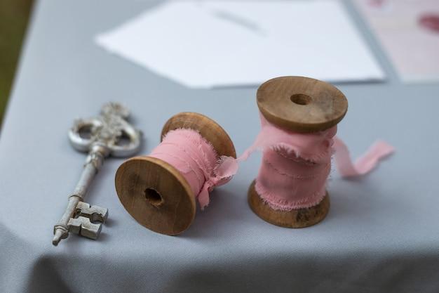 Свадебный крупный план деревенского декора, катушки с розовой лентой и старинным ключом