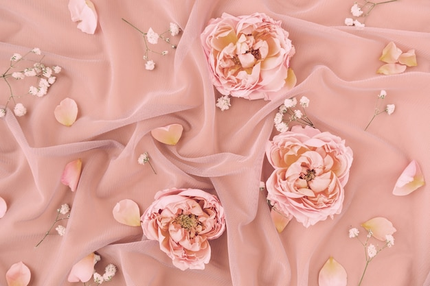 Wedding composition with pastel pink delicate tulle fabric with roses petals.